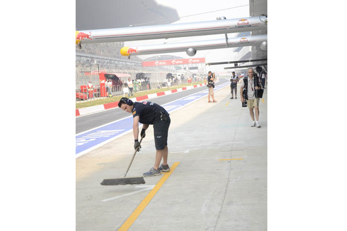 A Red Bull team member dusts the pit spot to ensure a clean getaway.